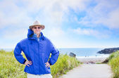 Caucasian man in forties wearing rain jacket by ocean shore — Stock Photo