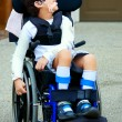 Seven year old biracial disabled boy in wheelchair — Zdjęcie stockowe #34426291