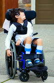 Seven year old biracial disabled boy in wheelchair — Stok fotoğraf
