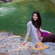 Foto Stock: Biracial teen girl sitting by river in norhtern Thailand