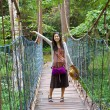 Teen girl on wooden hanging bridge in woods — Stock Photo #38884907