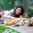 Teen girl playing with tiger cub inside cage — Stock Photo #38884943