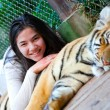 Stock Photo: Teen girl playing with tiger cub inside cage