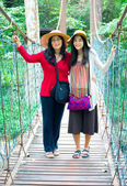 Asian mother and daughter standing on wooden hanging bridge in f — Stock Photo