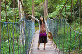Teen girl on wooden hanging bridge in woods — Stock Photo
