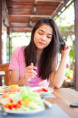 Teen girl eating breakfast on outdoor veranda — Stock Photo