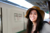 Smiling teen traveler waiting for train at station — Stock Photo