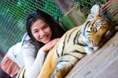 Teen girl playing with tiger cub inside cage — Stock Photo