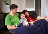 Family with disabled boy relaxing together on leather couch — Stock Photo