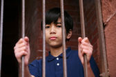 Boy standing behind bars — Foto de Stock