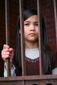 Unhappy girl standing behind bars — Stock Photo
