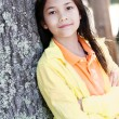 Photo: Young girl leaning against tree trunk, arms crossed