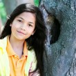 Stock Photo: Young girl leaning against tree trunk, arms crossed