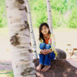Foto de Stock  : Young biracial girl sitting on rock under trees