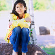 Young biracial girl sitting on rock under trees — Stockfoto #40656553