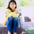 图库照片: Young biracial girl sitting on rock under trees