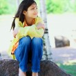 Photo: Young biracial girl sitting on rock under trees