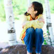 Young biracial girl sitting on rock under trees — Stock fotografie #40656595