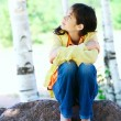 Stock Photo: Young biracial girl sitting on rock under trees