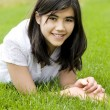 Young teen girl lying on green grass, relaxing — Stok Fotoğraf #40656667