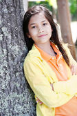 Young girl leaning against tree trunk, arms crossed — 图库照片