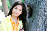 Young girl leaning against tree trunk, arms crossed — Photo
