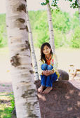 Young biracial girl sitting on rock under trees — Stock Photo