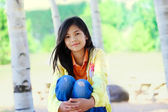 Young biracial girl sitting on rock under trees — Foto Stock
