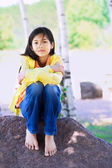Young biracial girl sitting on rock under trees — Stok fotoğraf