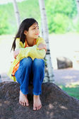 Young biracial girl sitting on rock under trees — Stock fotografie