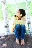 Young biracial girl sitting on rock under trees — Photo