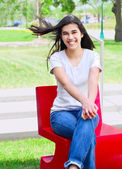 Beautiful teen girl sitting outdoors on red chair — Stockfoto
