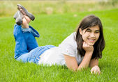 Young teen girl lying on green grass, relaxing — ストック写真