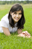 Young teen girl lying on green grass, relaxing — Stok fotoğraf