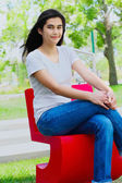 Beautiful teen girl sitting outdoors on red chair — Stok fotoğraf