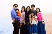 Multiracial family of seven on foggy beach — Stock Photo