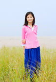 Girl standing in tall grassy field — Stock Photo