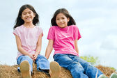 Two young girls sitting on top of haybale — Stock Photo