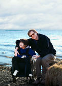 Father sitting with disabled son along lake shore — Stock Photo