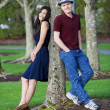 Young interracial couple standing by tree — Stock Photo