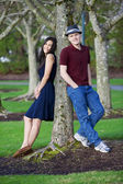Young interracial couple standing by tree — ストック写真