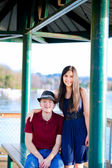 Young woman standing next to seated young man by a lake — Stock Photo