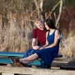 Young interracial couple enjoying time together on wooden pier o — Stock Photo #43851211