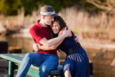 Young interracial couple sitting together on dock over lake — Foto Stock