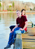 Beautiful interracial couple sitting on wooden dock over lake — Stock Photo