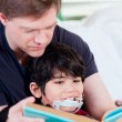Father reading book to disabled little son — Stock Photo #48070687