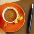 Orange coffee cup on brown writing paper with pen — Stock Photo