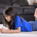 Little girl doing her homework on floor — Stock Photo #48070863