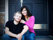 Young interracial couple sitting on front steps  — 图库照片