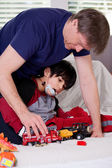 Handsome father playing cars with disabled son — Stock Photo